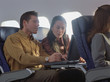 Young woman and man using laptop on airplane