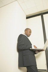 Businessman using laptop standing