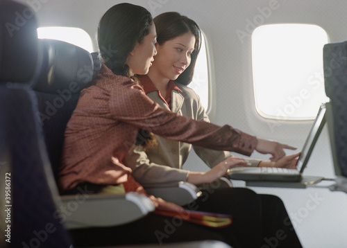 Young women using laptop on airplane