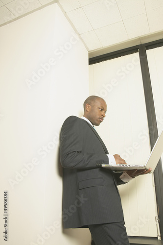Businessman using laptop standing