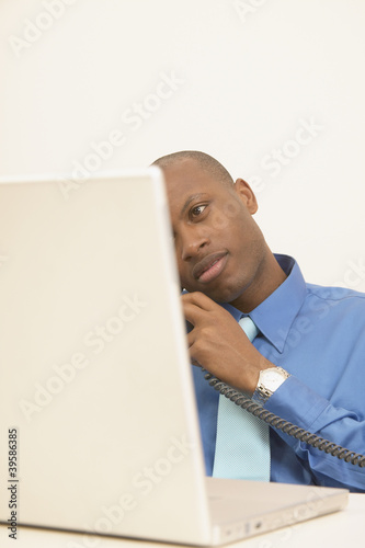 Businessman taking phone call and using laptop