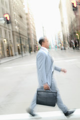 Blurred businessman walking across street