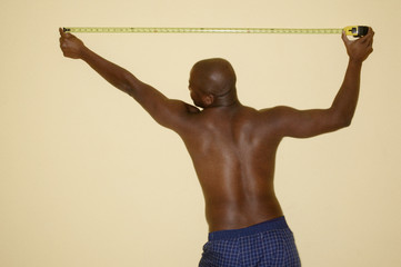 Rear view of man measuring wall