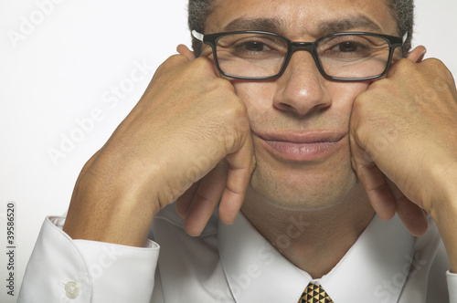 Portrait of a young businessman sitting with his hands on his cheeks