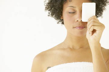 Woman wrapped in towel holding soap over eye