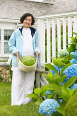 Portrait of woman carrying watermelon in basket