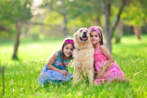 Two young girls hugging golden retriever in the park
