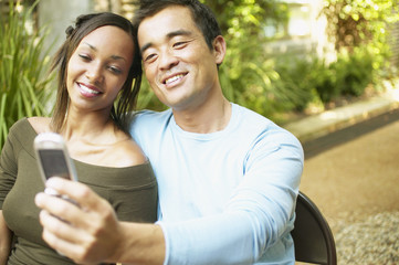 Couple taking self-portrait with cell phone