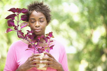 Woman holding plant with eyes closed