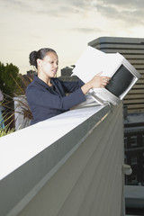 Businesswoman dropping computer monitor over balcony