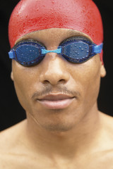 Close up portrait of man wearing goggles and swimming cap