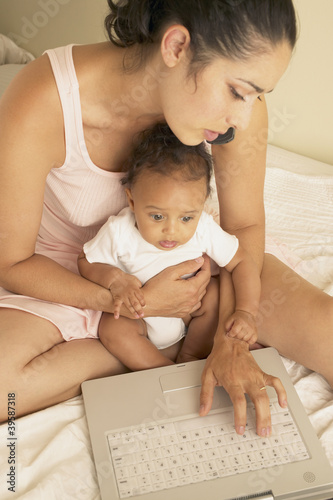 Mother holding baby and typing on laptop