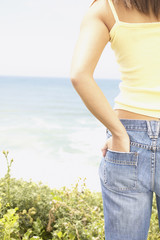 Midsection of woman looking at ocean