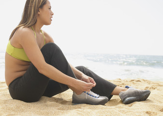 Woman tying shoe at beach