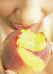 Close up of woman biting peach