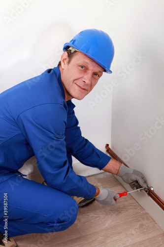 Man attaching copper pipe to wall