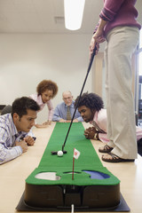 Businesspeople playing golf in office
