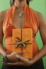 Midsection of woman with wrapped gift