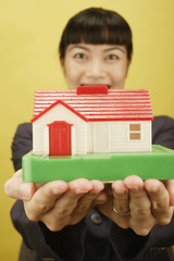 Businesswoman holding house model
