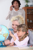 Woman helping her daughter complete her  geography homework
