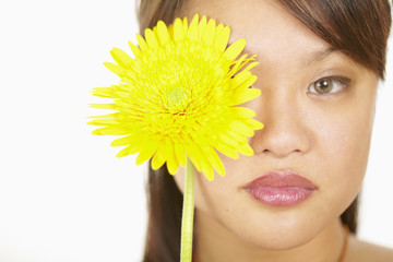 Close up of woman holding flower over eye