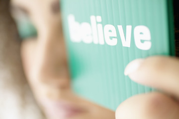 Woman holding believe sign