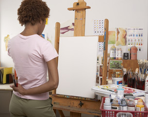 Rear view of female artist looking at canvas