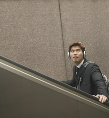Man with headphones riding escalator