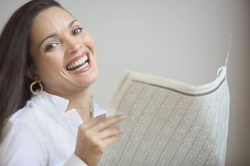Portrait of businesswoman laughing while holding newspaper