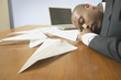 Businessman sleeping with paper airplanes on desk