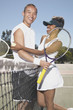 Portrait of couple hugging on tennis court