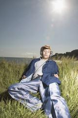Teenage boy laying in grass wearing headphones