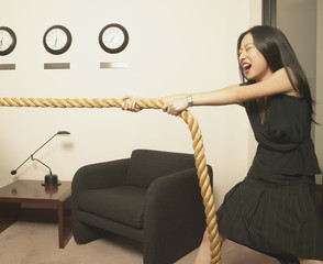 Businesswoman pulling rope in office