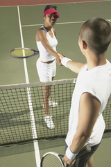Players shaking hands on tennis court