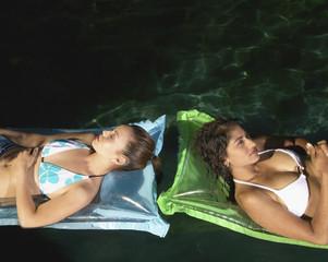 Two women sunbathing on air mattresses
