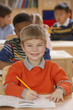 Portrait of boy working at desk in classroom