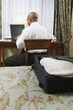 Businessman with laptop at desk in hotel