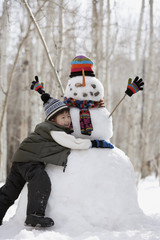 Boy hugging snowman