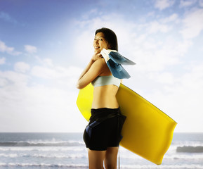 Portrait of woman with body board at beach