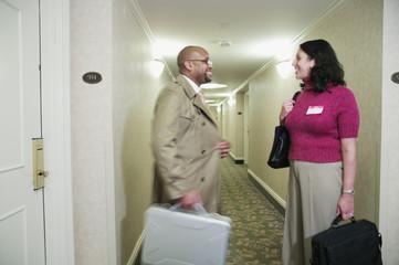 Two businesspeople talking in hotel hallway