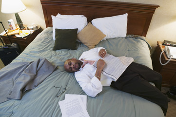 Businessman laying on hotel bed with newspaper
