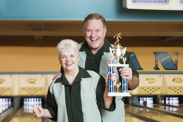 Couple with trophy at bowling alley