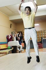 Man cheering at bowling alley