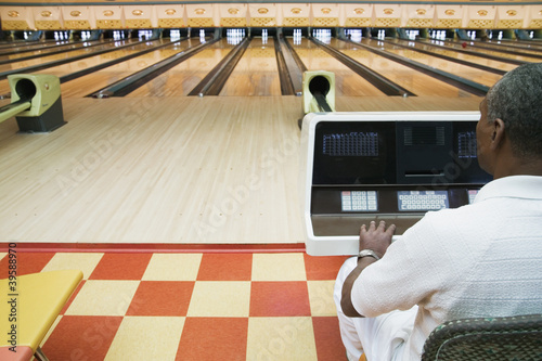 Man keeping score at bowling alley