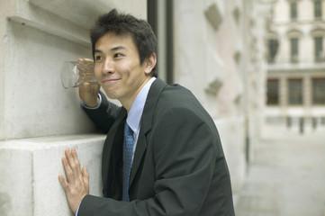 Businessman listening through glass on wall
