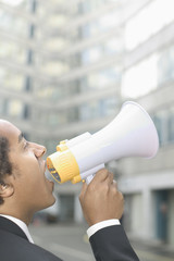 Businessman talking through megaphone outdoors