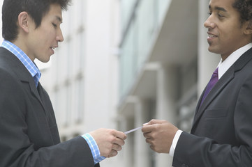 Profile of businessmen exchanging cards