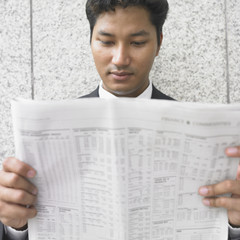 Close up of businessman reading newspaper