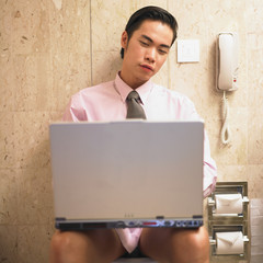 Businessman working on laptop while sitting on toilet