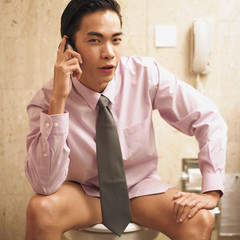 Businessman talking on phone while sitting on toilet